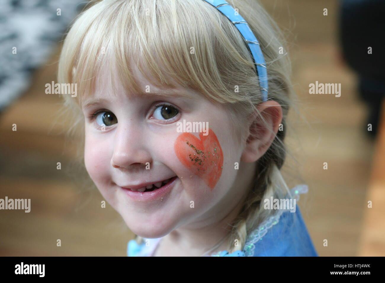 Little blonde girl dressed up as Disney Cinderella, facepaint, innocent concept, childhood concept - Stock Image