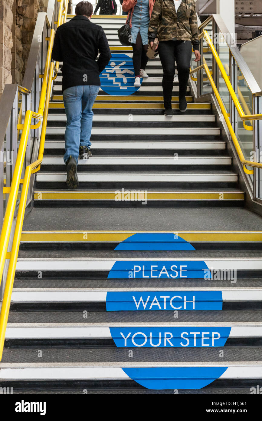 'Please watch your step' sign on steps. Safety advice for people to take care while using stairs at Sheffield - Stock Image