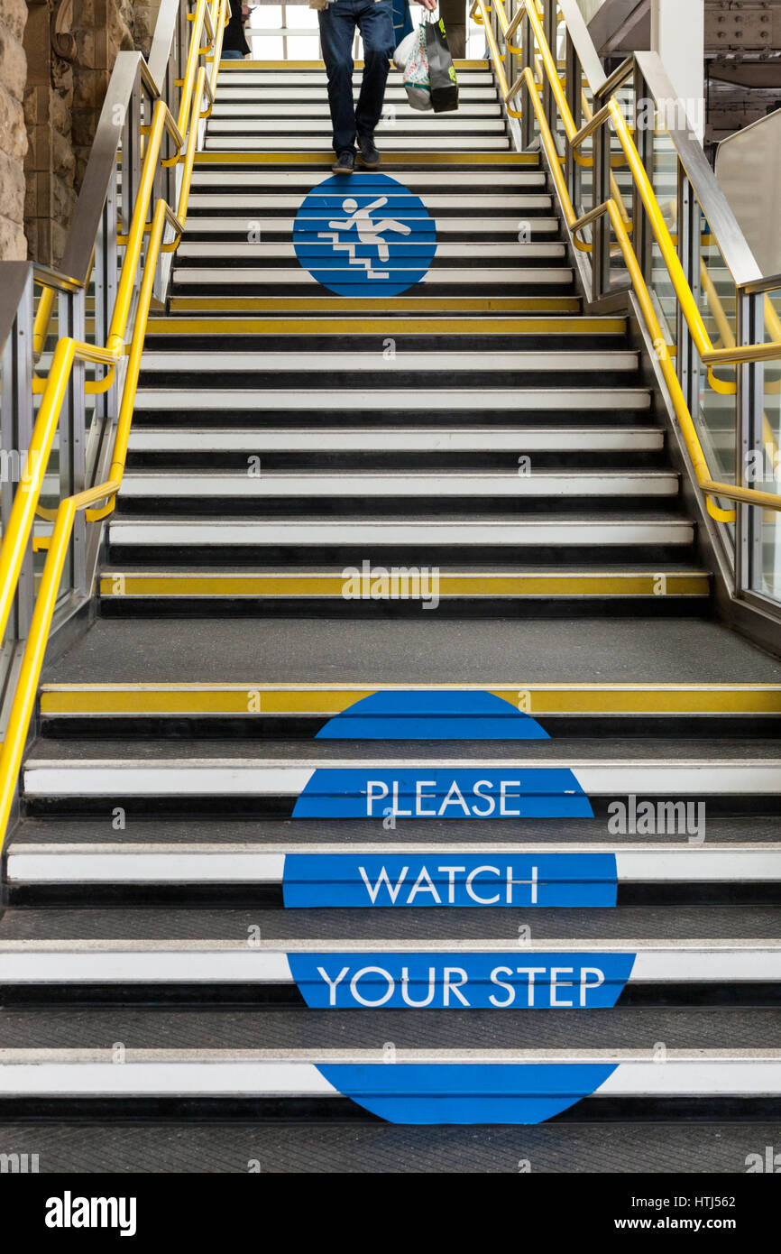 'Please watch your step' sign on stairs. Safety advice for people to take care while using steps at Sheffield - Stock Image