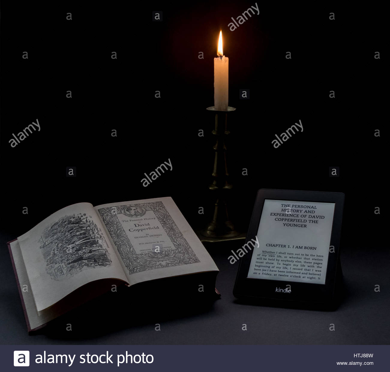 New vs Old, the same Dickens novel on a Kindle and in Hardback illuminated by a candle against a black background. Stock Photo