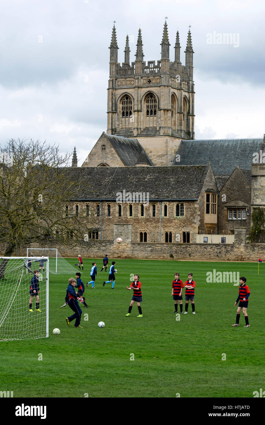 Merton College chapel with schoolchildren practising football in the foreground, Oxford, UK - Stock Image