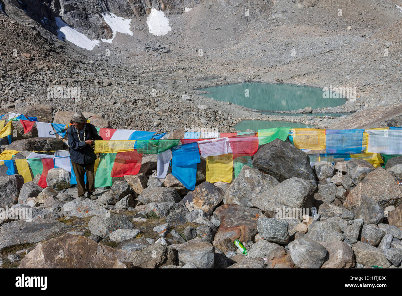 Tibetan Buddhist man pilgrim tying the Lung ta prayer flags at Dolma La pass en route Mt. Kailash Kora - Stock Image