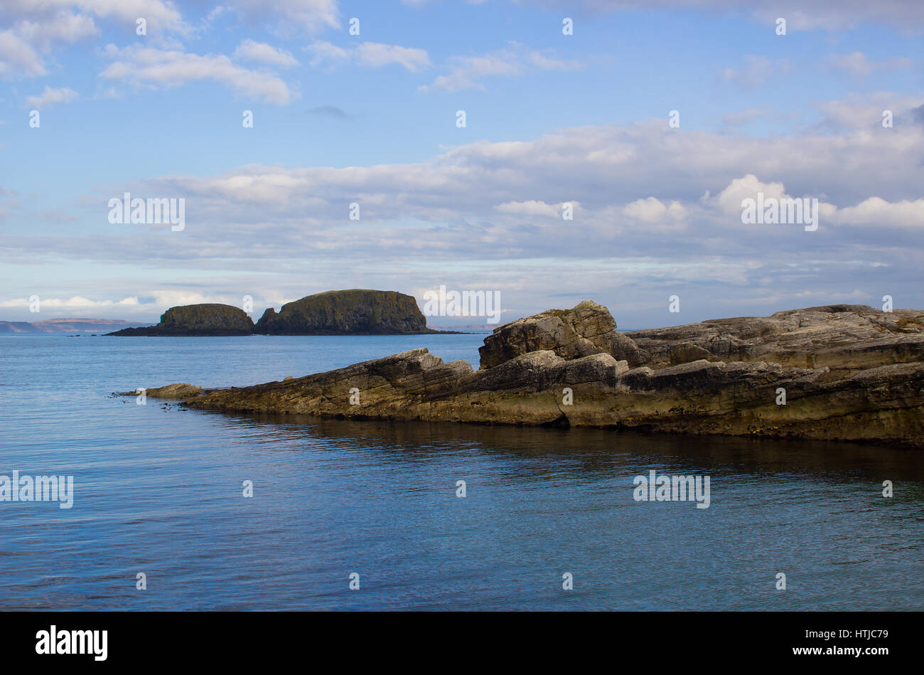 The small harbor at Ballintoy on the North Antrim coast of Northern ireland with its stone built boathouse reflecting - Stock Image