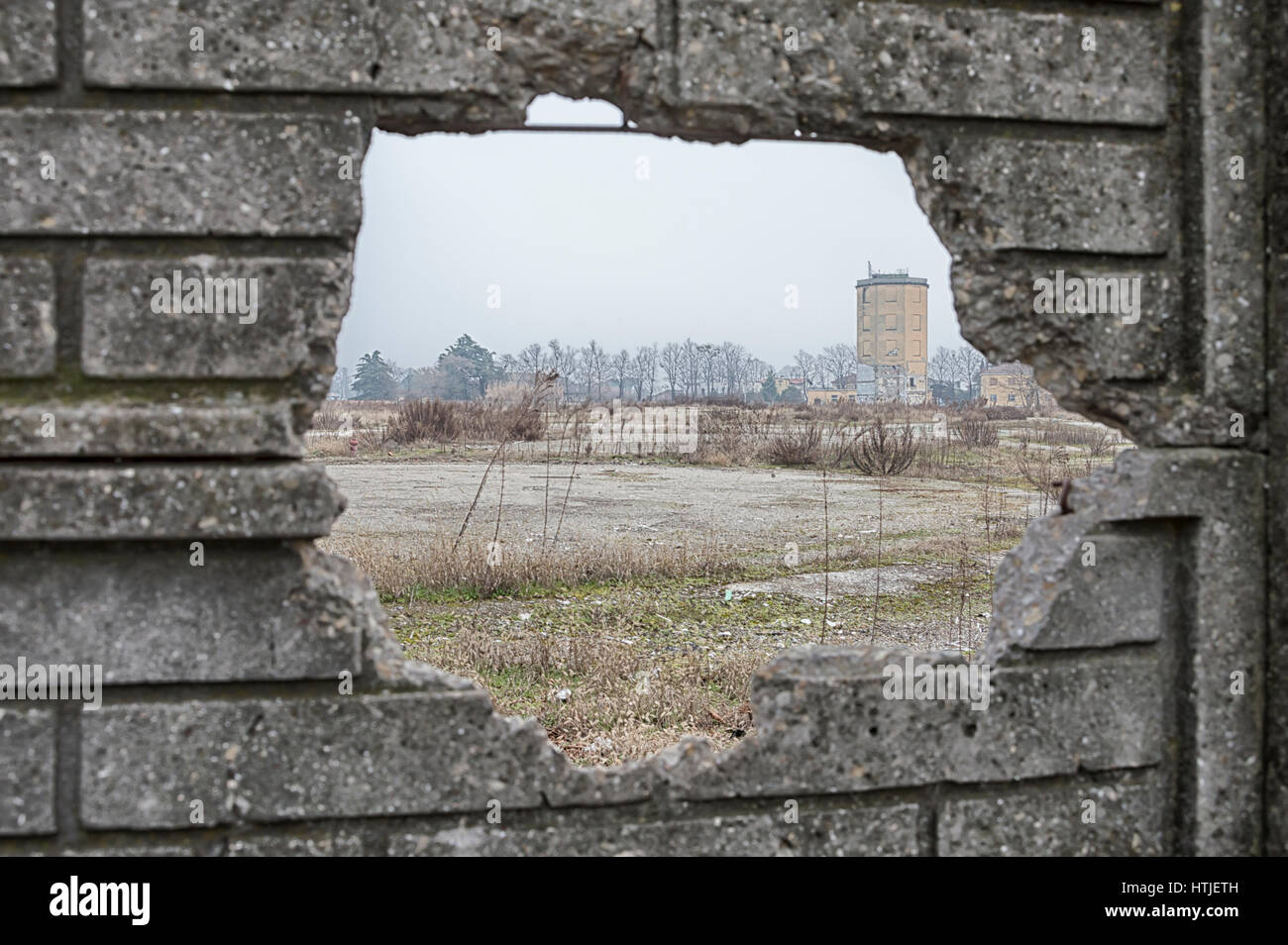 Ruins of an old factory in a wasteland, view through broken wall - Stock Image