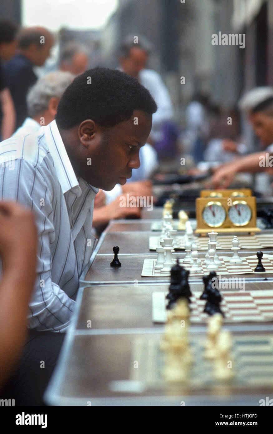 Man playing chess at street concession in New York City - Stock Image