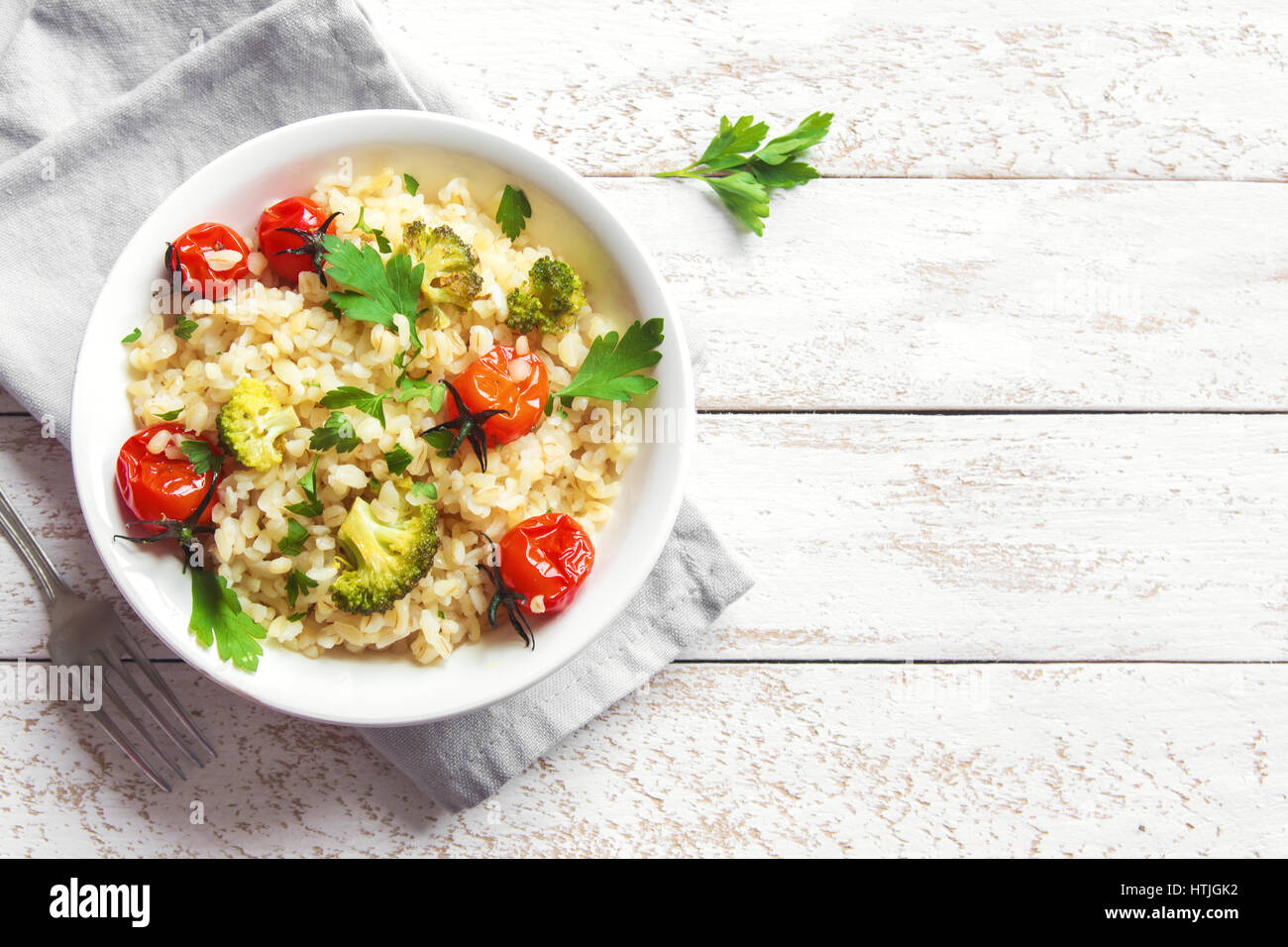 Bulgur with Vegetables: tomatoes, broccoli and parsley on white wooden background - healthy homemade organic vegan Stock Photo