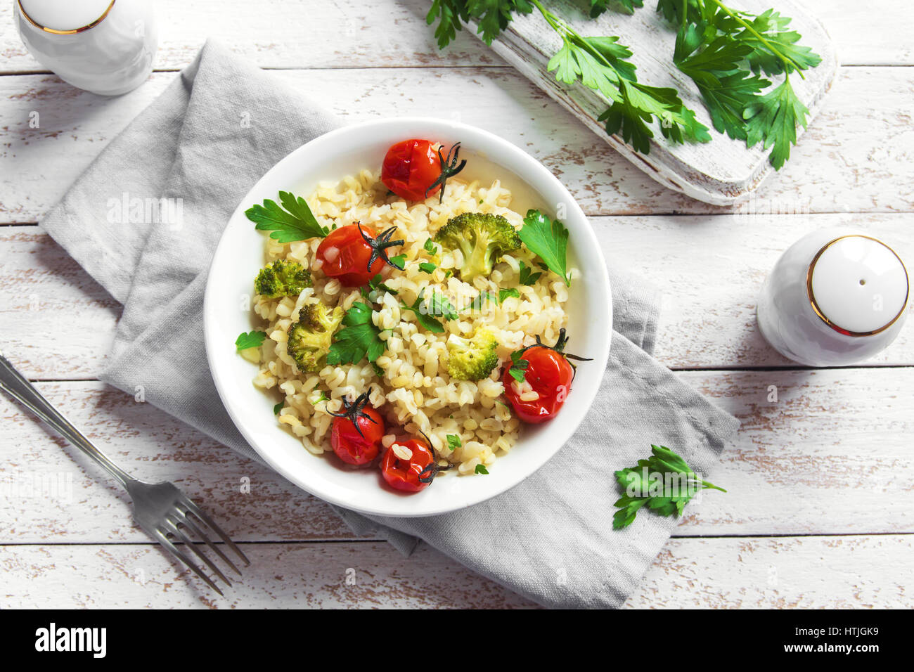 Bulgur with Vegetables: tomatoes, broccoli and parsley on white wooden background - healthy homemade organic vegan - Stock Image