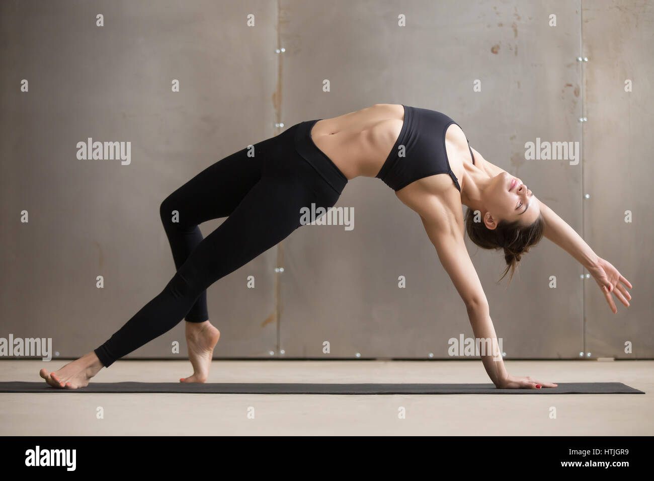 Young attractive woman stretching in Camatkarasana pose, grey st - Stock Image