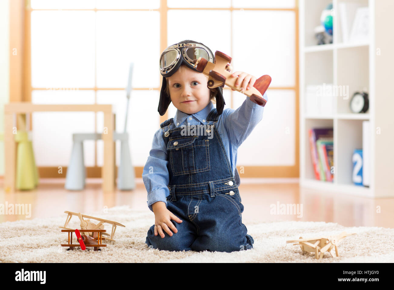 Child pretending to be aviator. Kid playing with toy airplanes at home - Stock Image