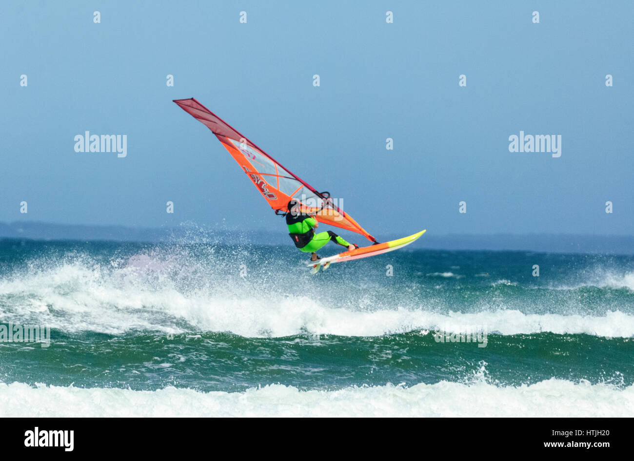 Windsurfer jumping over a big wave at Seven Mile Beach, Gerroa, Illawarra Coast, New South Wales, NSW, Australia Stock Photo
