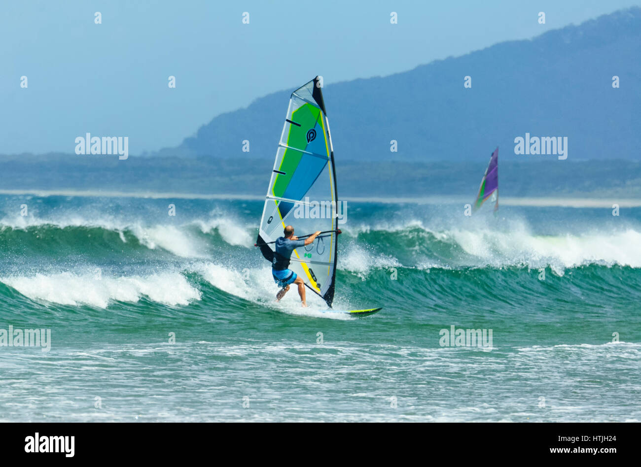 Windsurfer surfing in heavy seas with large waves at Seven Mile Beach, Gerroa, Illawarra Coast, New South Wales, Stock Photo