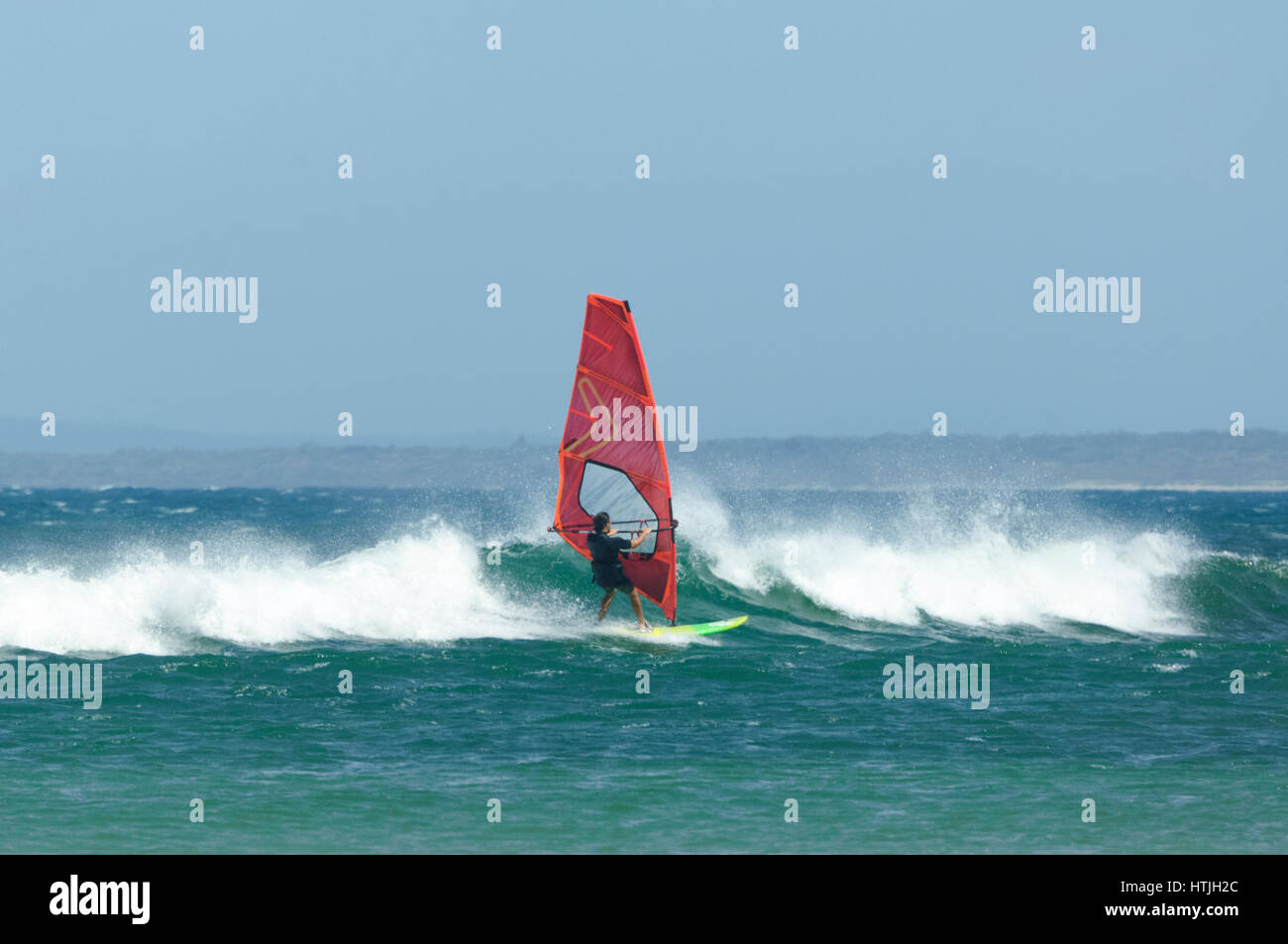 Windsurfer with colourful sails and surfboard at Seven Mile Beach, Gerroa, Illawarra Coast, New South Wales, NSW, - Stock Image