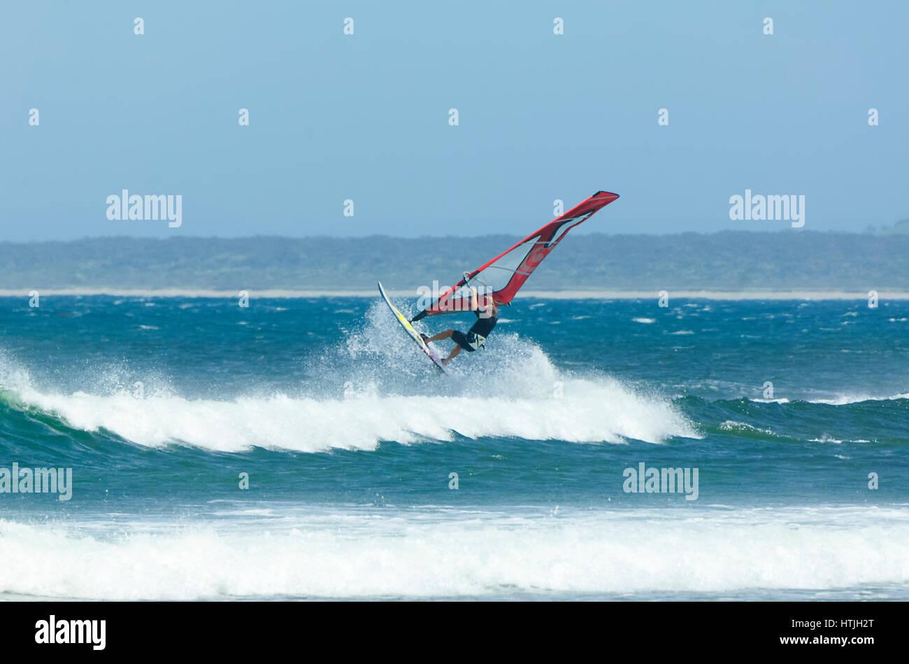 Windsurfer jumping over a big wave at Seven Mile Beach, Gerroa, Illawarra Coast, New South Wales, NSW, Australia - Stock Image