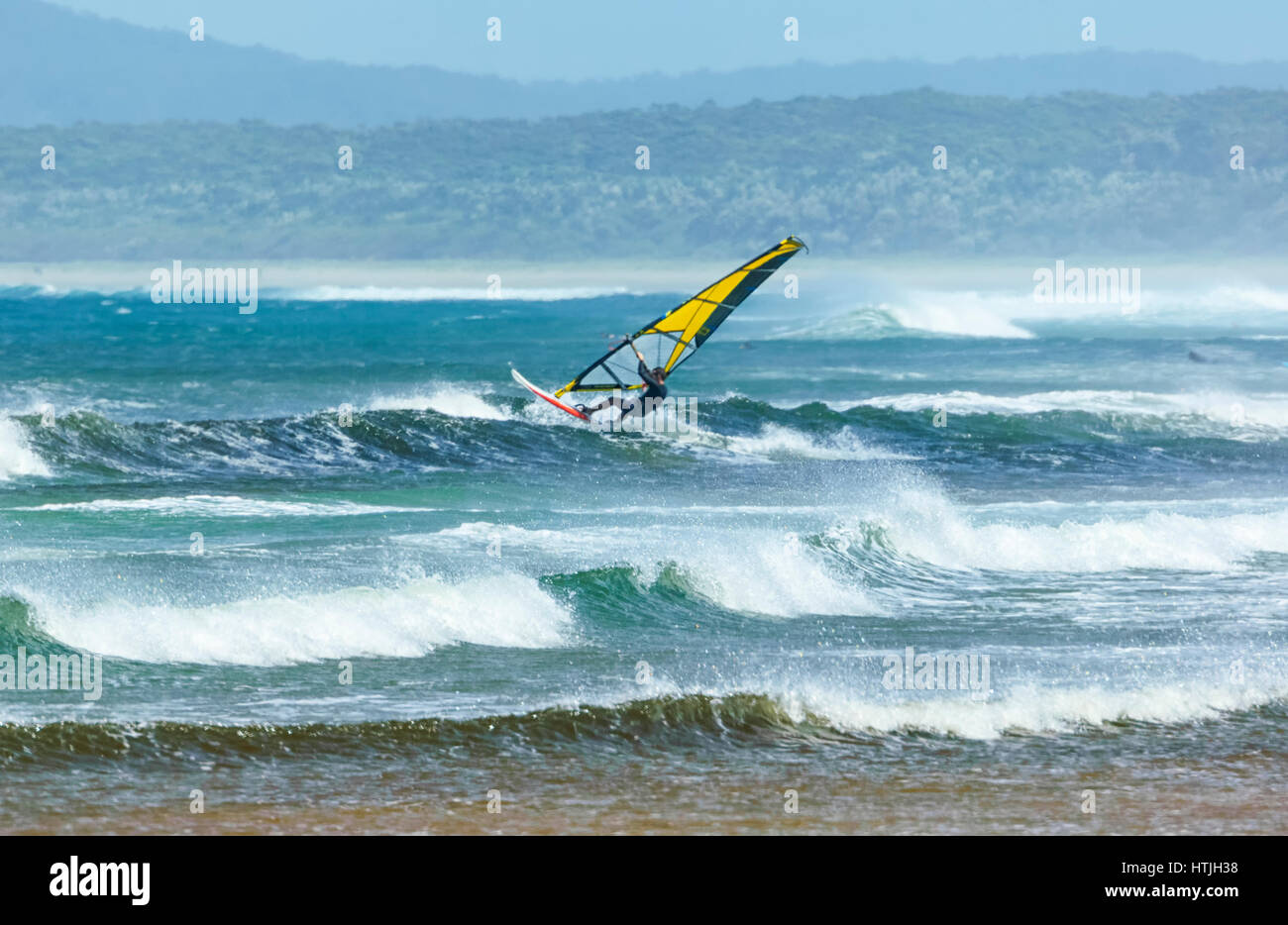 Windsurfer surfing in heavy seas with large waves at Seven Mile Beach, Gerroa, Illawarra Coast, New South Wales, - Stock Image