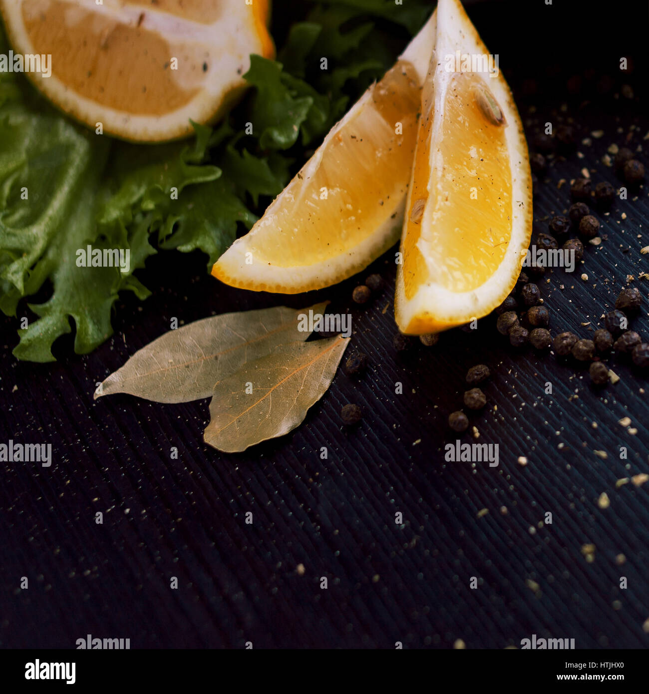 Black food background with slices of lemon, fresh aromatic herbs and spices, copy space, top view - Stock Image