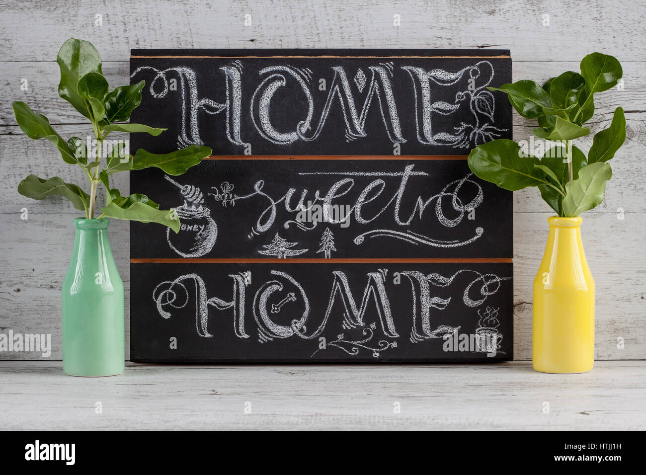 Hand lettering calligraphy sign drawn with chalk. Lettered quote 'Home sweet home' to use as decoration - Stock Image
