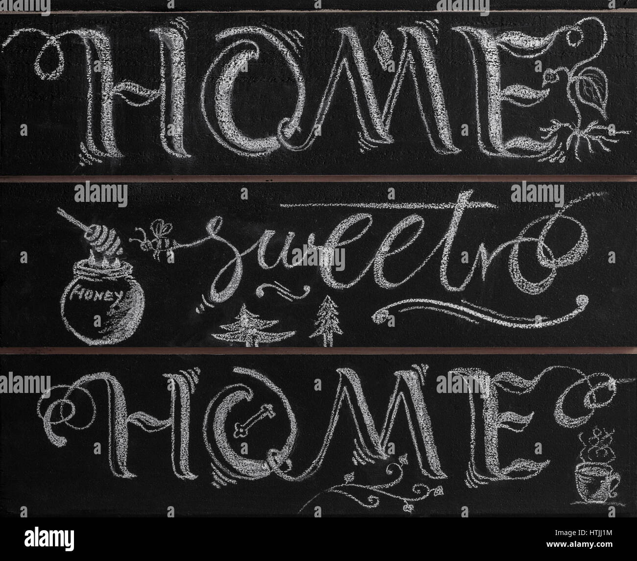 Hand lettering calligraphy sign drawn with chalk. Lettered quote 'Home sweet home' - Stock Image