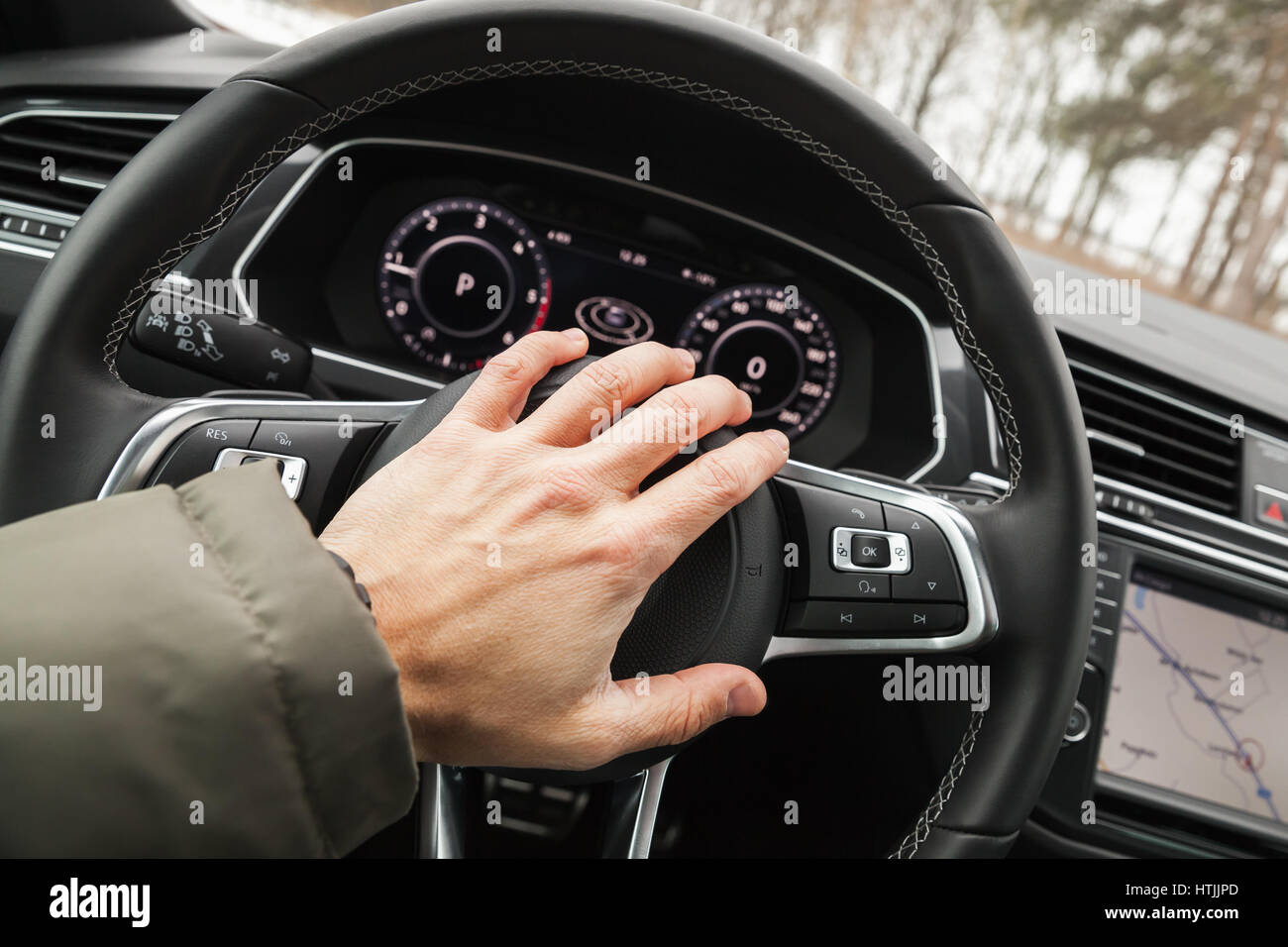 Driver hand pushes a steering wheel klaxon of luxury car. Closeup photo with selective focus - Stock Image