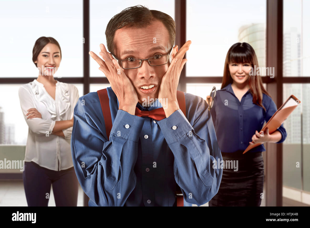 Geeky asian businessman standing in front of his team working at office - Stock Image