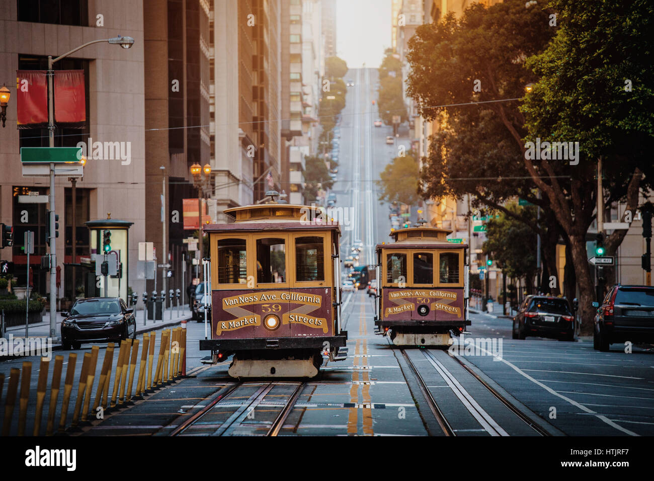 Classic view of historic traditional Cable Cars riding on famous California Street in early morning light at sunrise, - Stock Image