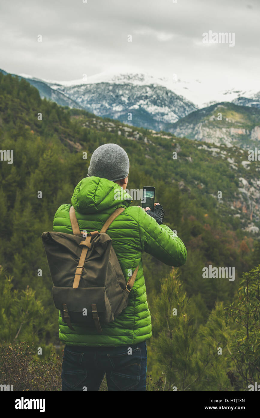 Young man traveller wearing bright clothes making photo of landscape - Stock Image