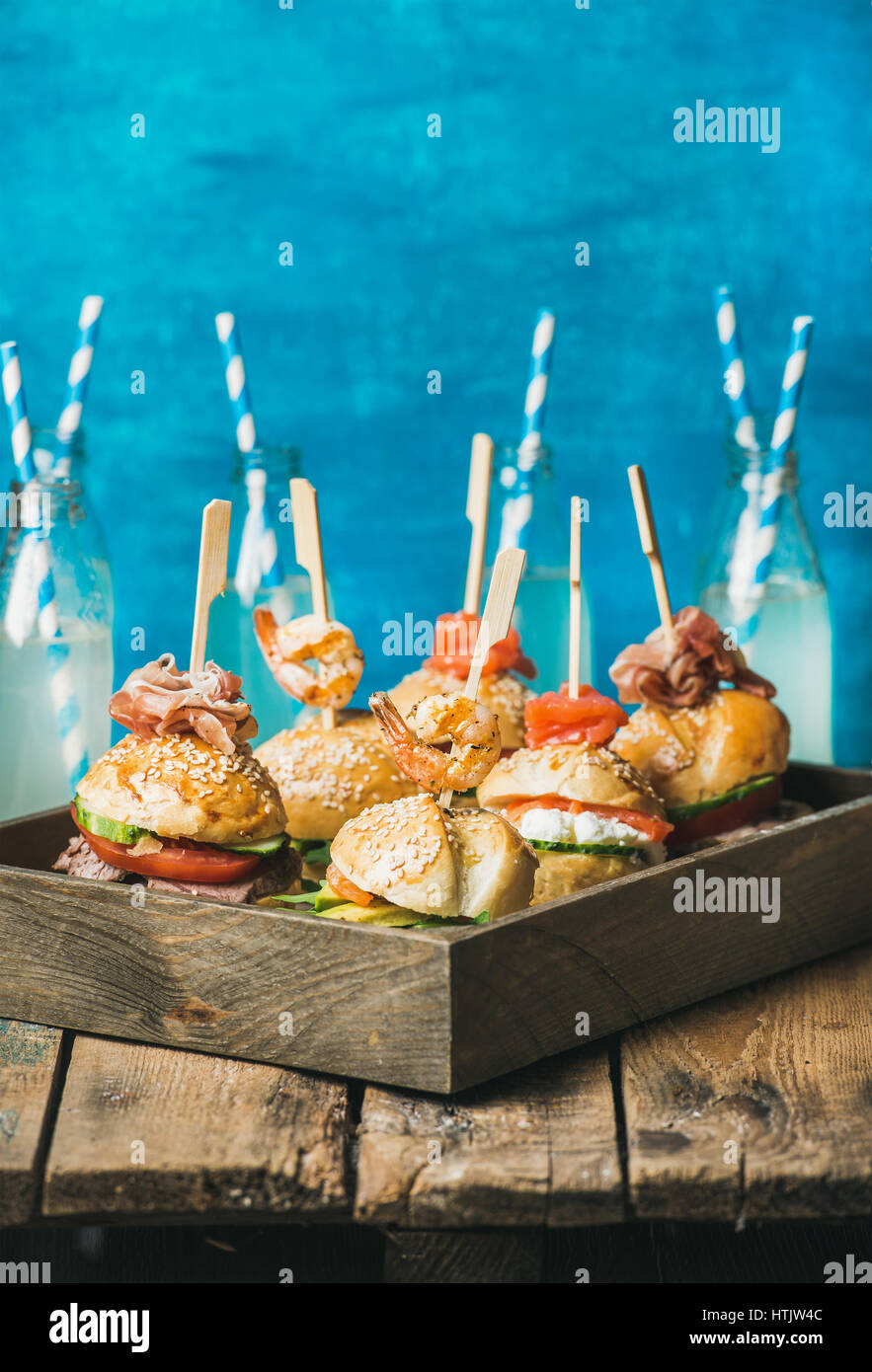 Different homemade burgers in wooden tray and lemonade in bottles - Stock Image