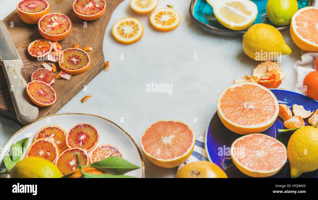 Natural fresh citrus fruits in ceramic plates and wooden board - Stock Image