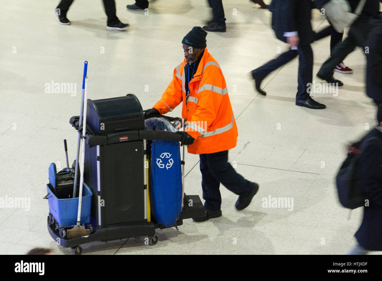 An elderly station cleaner at Waterloo Station during rush-hour, London, SE1, UK - Stock Image
