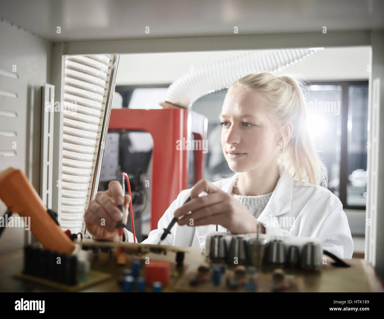Young woman with white lab coat measuring controller with meter, Austria - Stock Image
