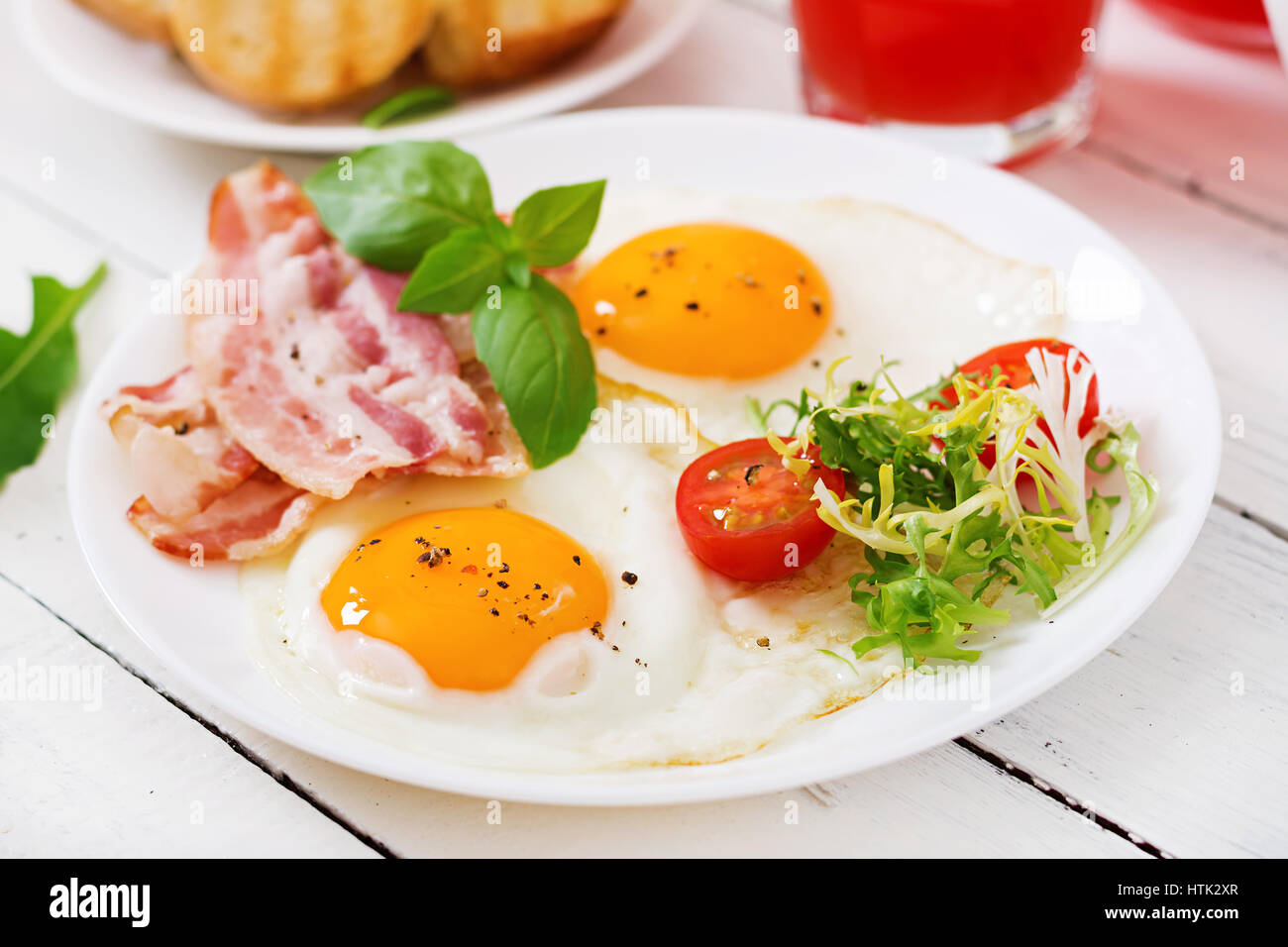 English breakfast - fried egg, tomatoes and bacon. - Stock Image