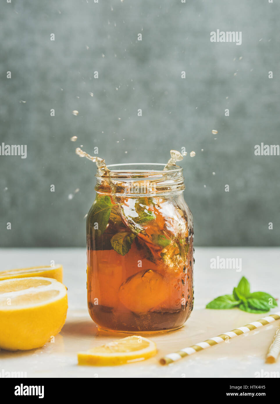 Summer Iced tea with lemon and herbs, copy space - Stock Image