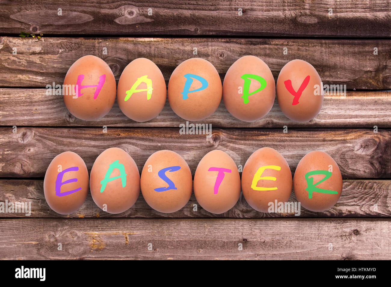 Happy easter written on eggs on wooden planks background - Stock Image