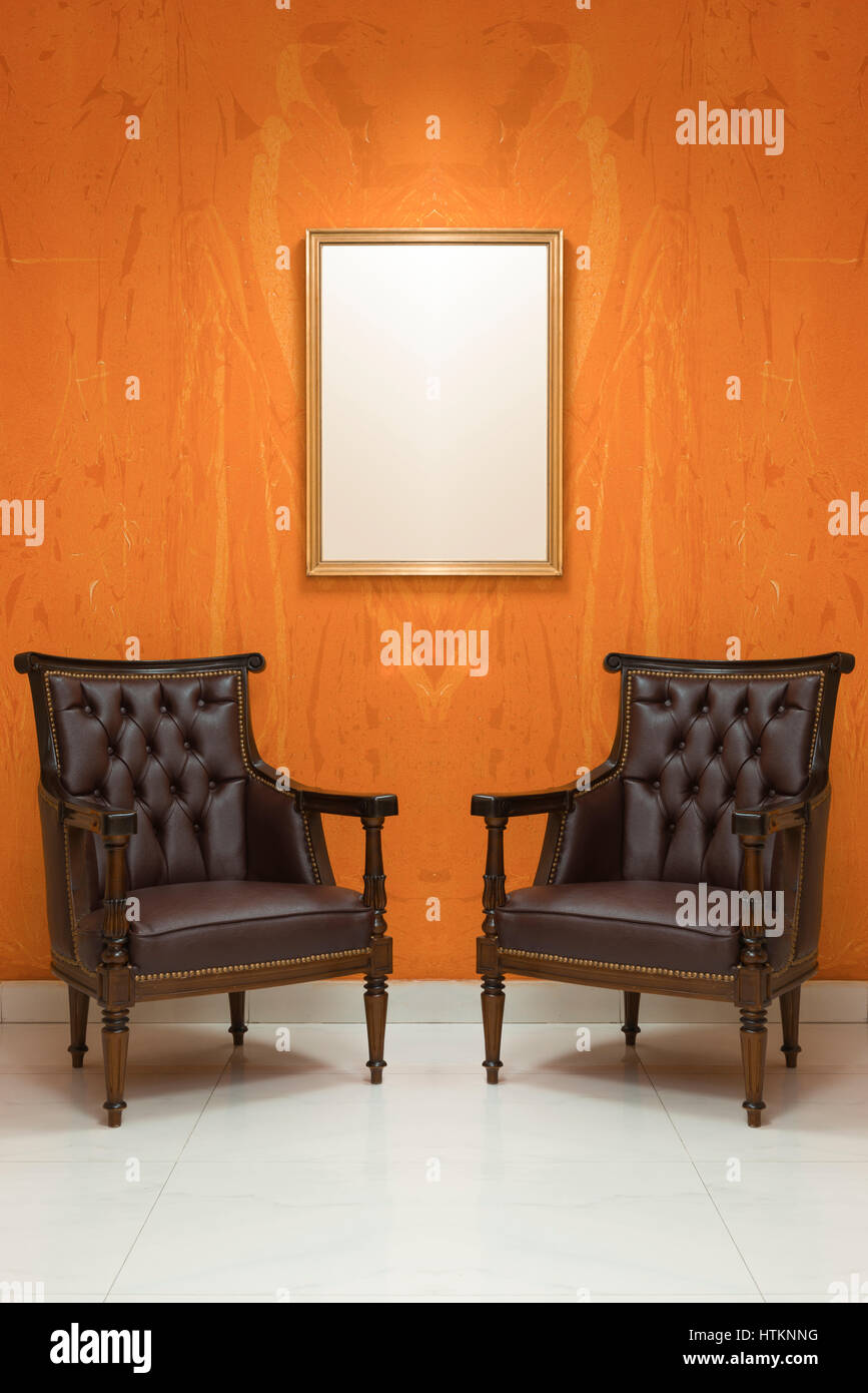 Two Empty Chairs In A Living Room With Orange Wall Background