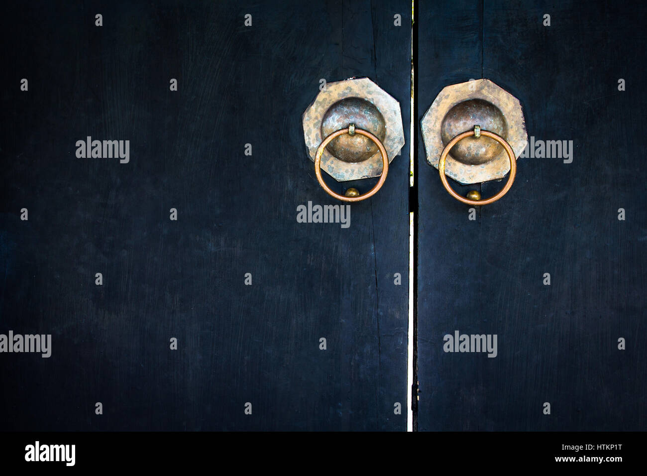 Old lockpad locked on a wooden blue door with rusty chain close up background. Stock Photo