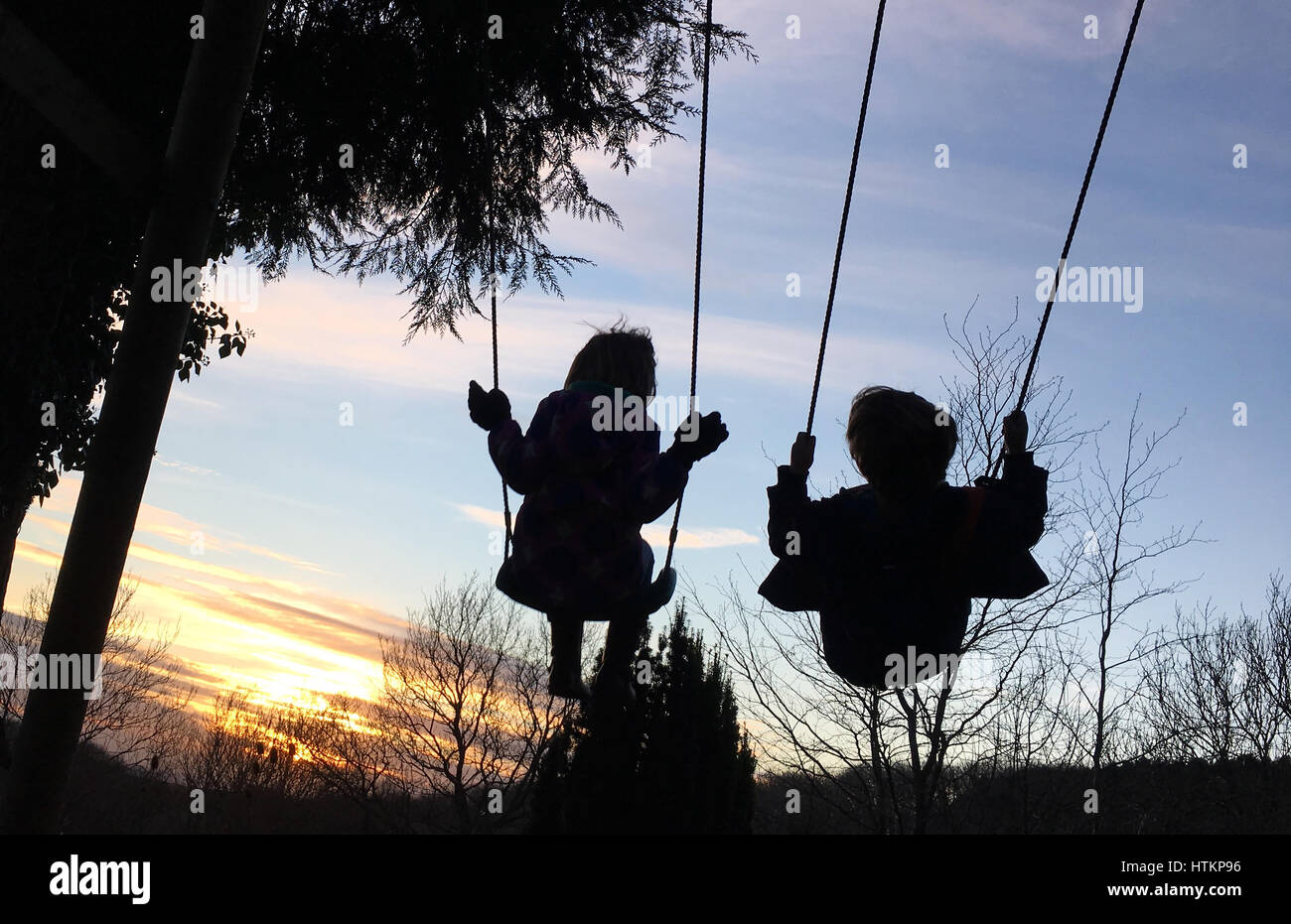 Two children on swings silhouetted against an evening sky - Stock Image