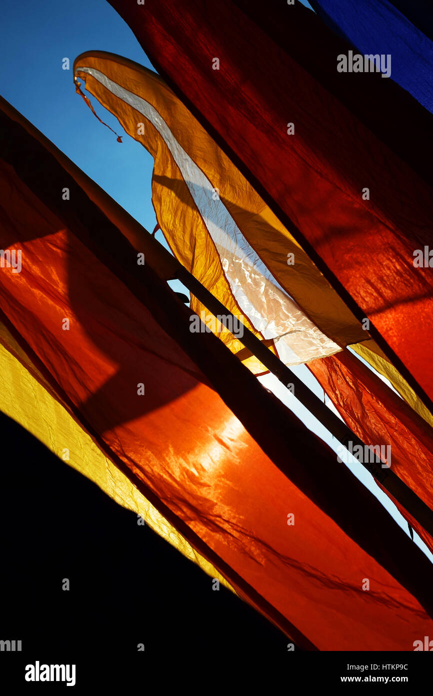 Brightly coloured banner flags flapping against blue sunny sky - Stock Image