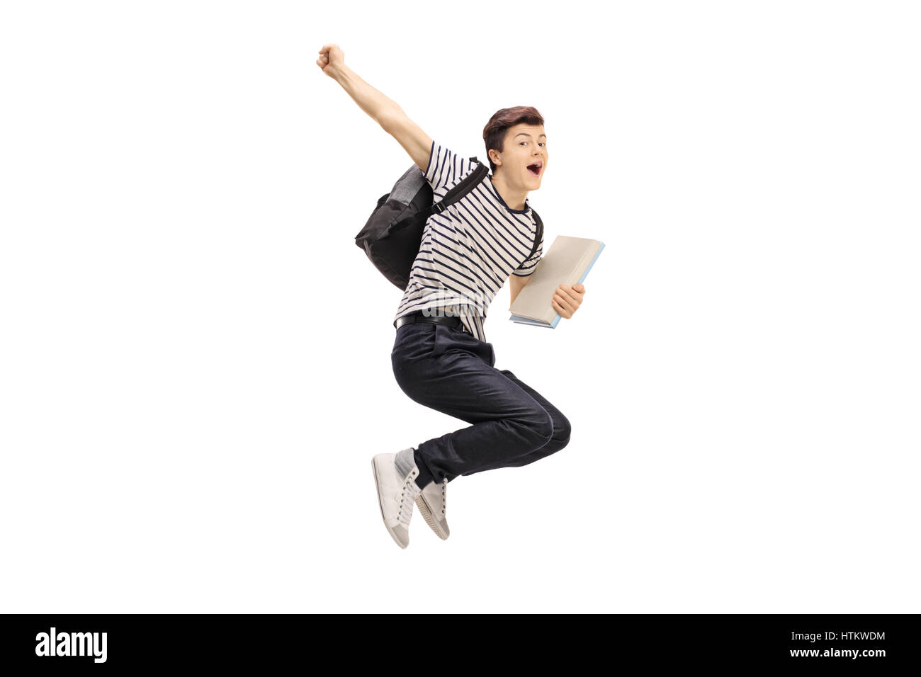 Overjoyed teenage student jumping and gesturing happiness isolated on white background - Stock Image
