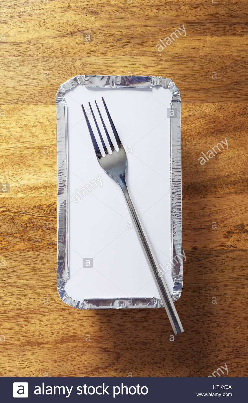 Silver foil takeaway tray with a fork placed on top. Shot from above on wooden table - Stock Image