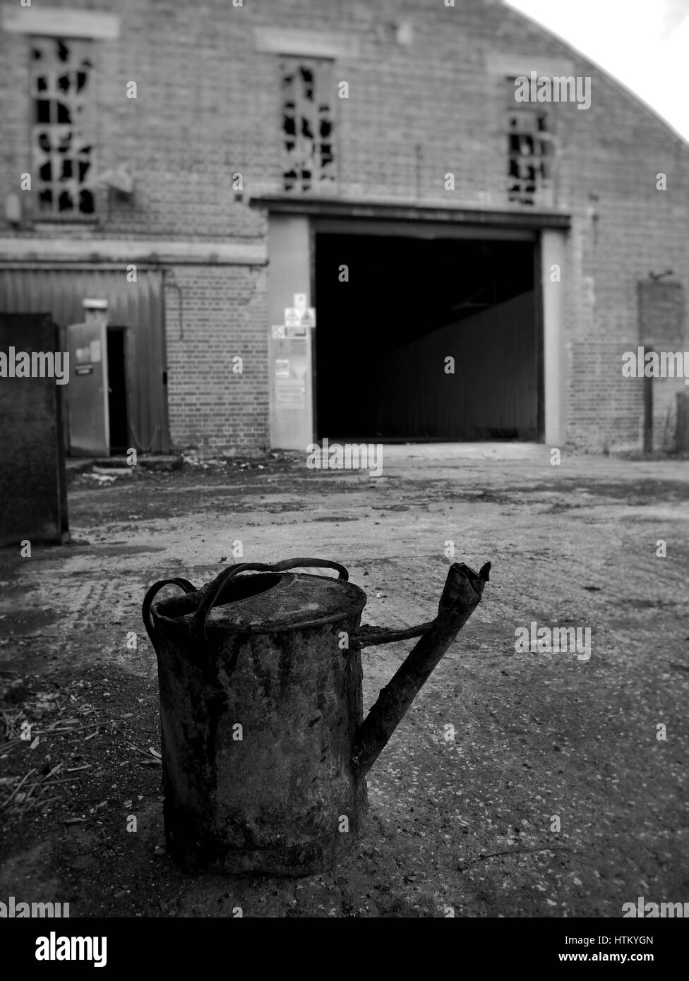 Rusty watering can in abandoned factory UK - Stock Image
