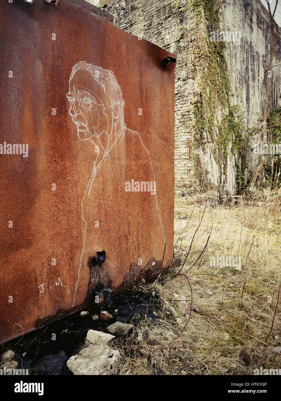 Street art - Industrial artwork - Chalk drawing of old man on rusty container in Derbyshire quarry Stock Photo