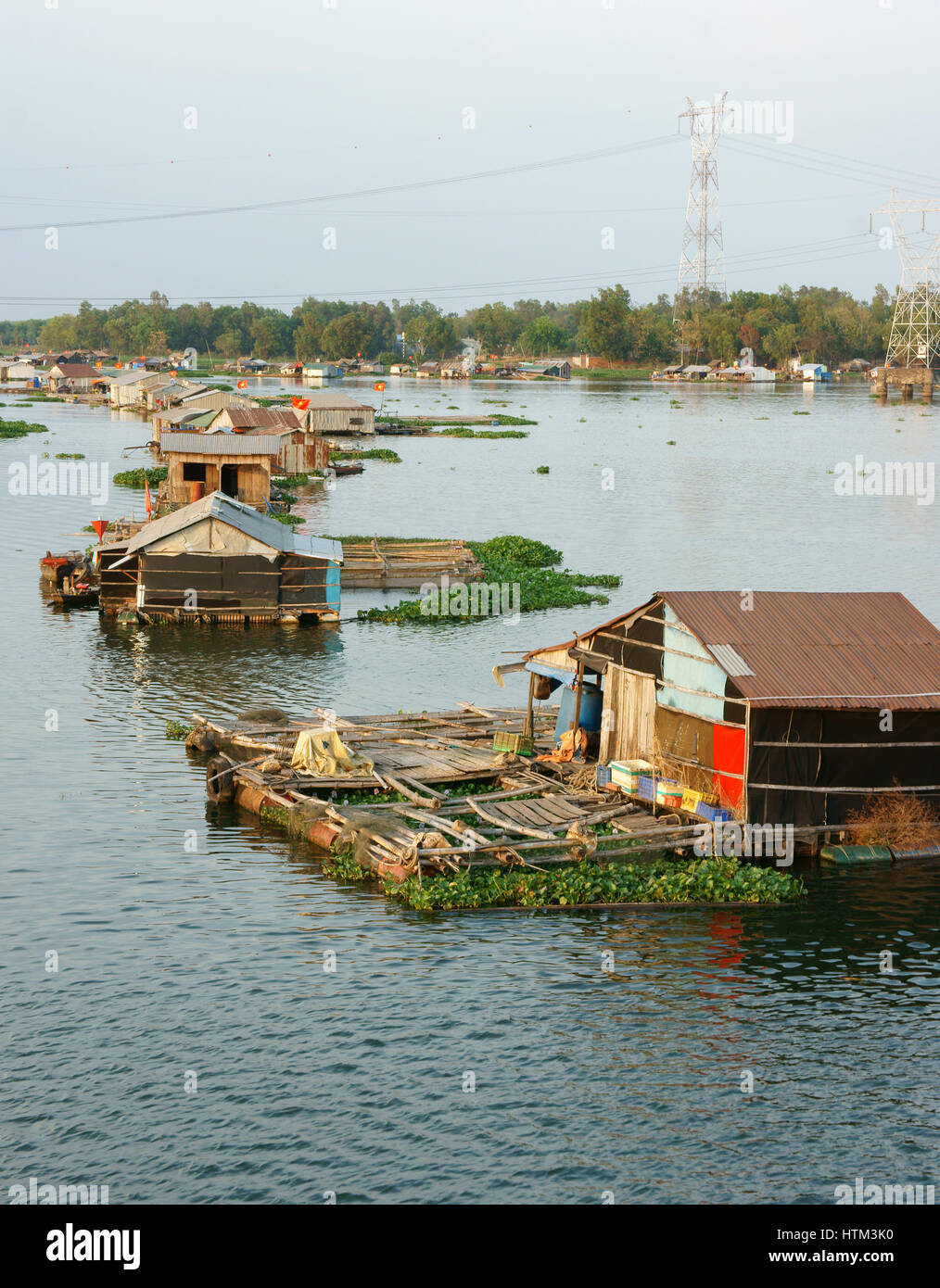 DONG NAI, VIET NAM, Life of Asian fisherman on La Nga river, floating house in residence of fishing village with - Stock Image