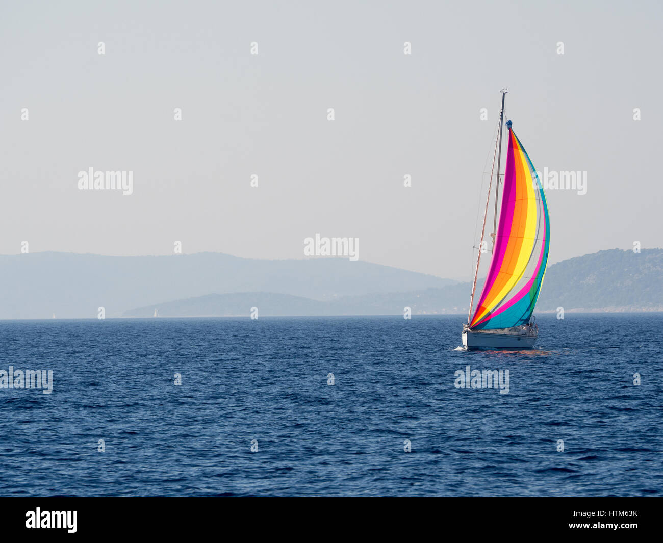 a yacht sailboat boat with multicoloured multicolored sail sails sailing on the sea ocean Mediterranean blue sky - Stock Image