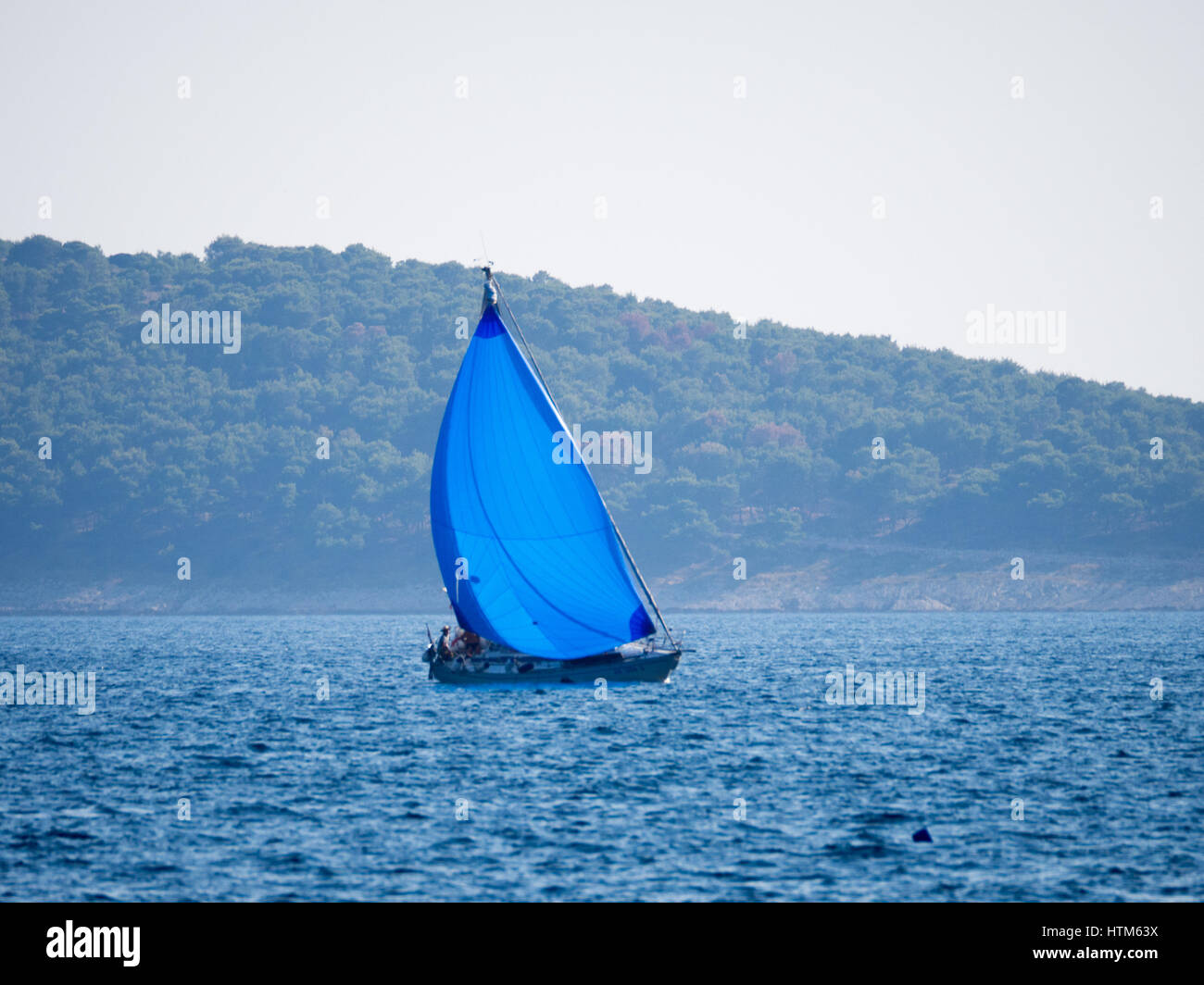 a yacht sailboat boat with blue sail sails sailing on the sea ocean Mediterranean under a blue sky  on calm waters - Stock Image