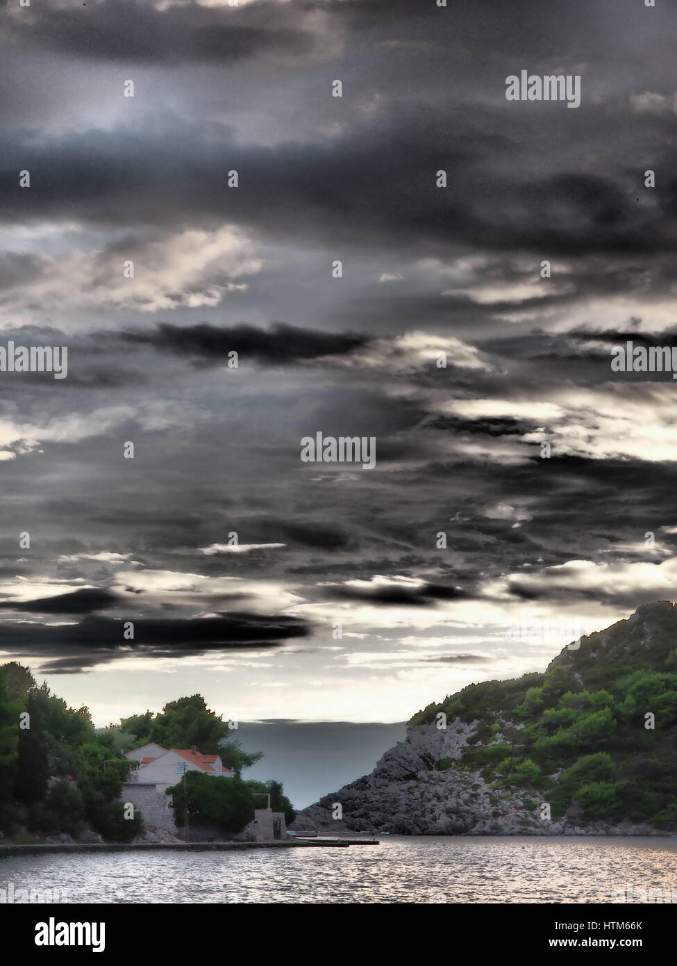 An angry stormy storm dark sky with clouds above a rocky island outcrop with trees and red roof house, Sipan Croatia - Stock Image