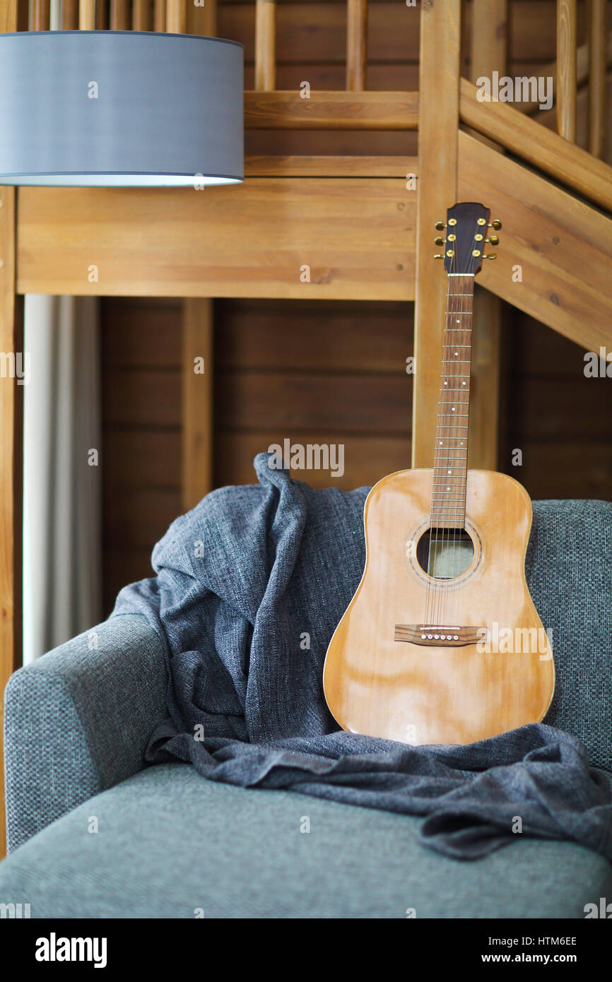 Cozy living room with guitar on the sofa in the wooden house Stock Photo