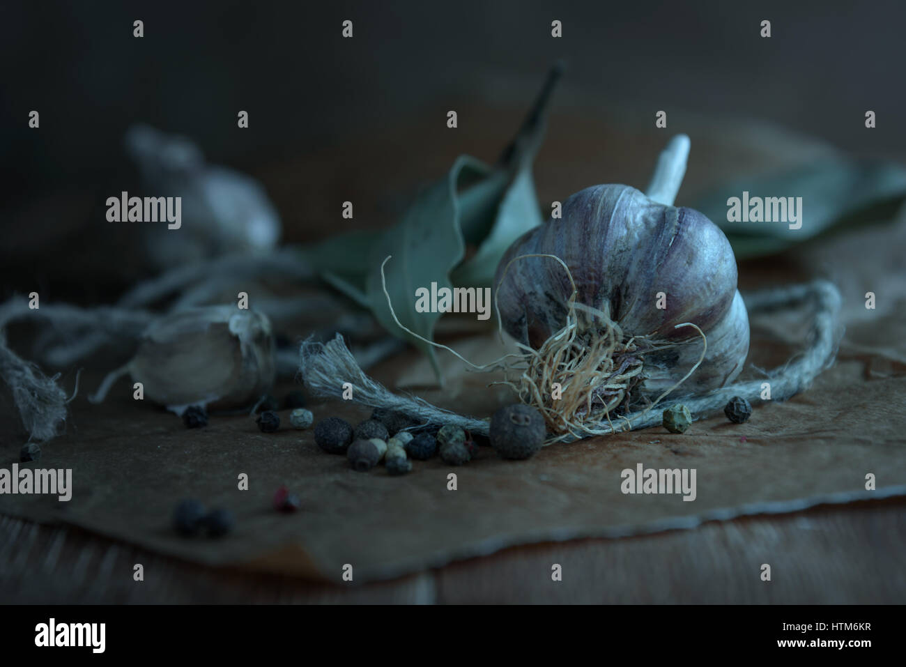 head garlic, scattered pepper, twine on a wooden table in rustic style as a cooking concept - Stock Image