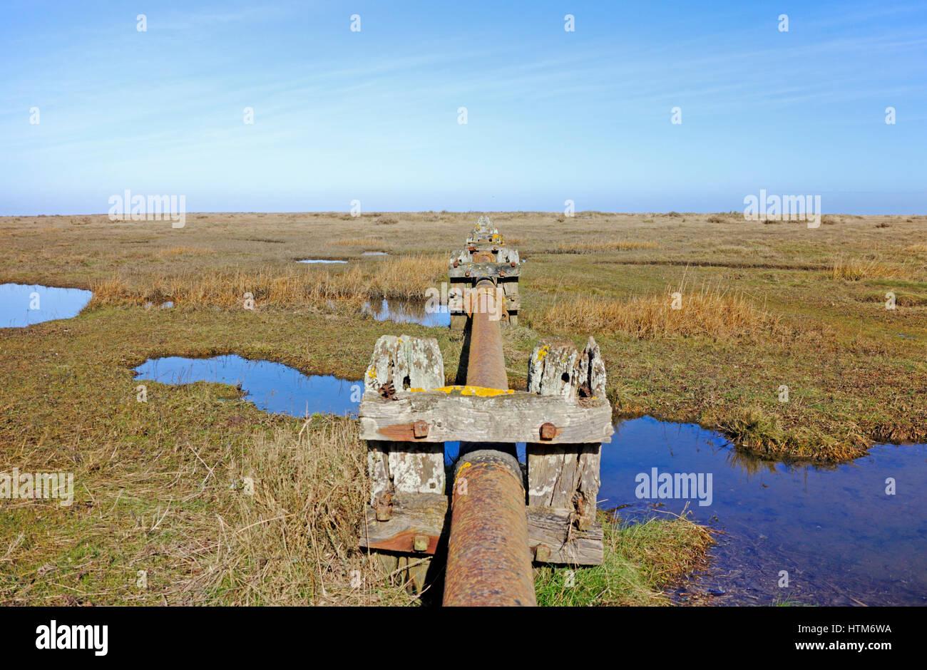 A view of mature salt marsh with disused sewage pipe on the North Norfolk coast at Stiffkey, Norfolk, England, United - Stock Image