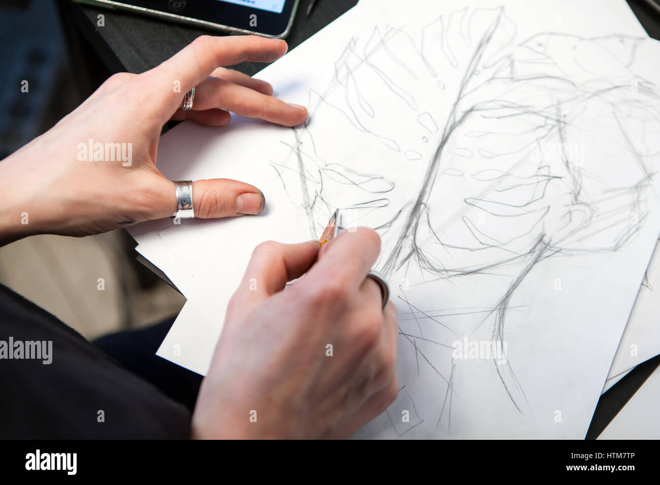 Girl tattoo artist draws a sketch. Close-up of hands Stock Photo