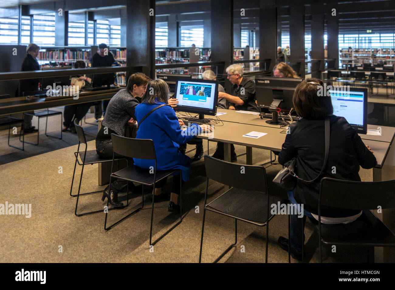 Visitors watching computer screens at De Krook, new public library in the city center of Ghent, East Flanders, Belgium - Stock Image