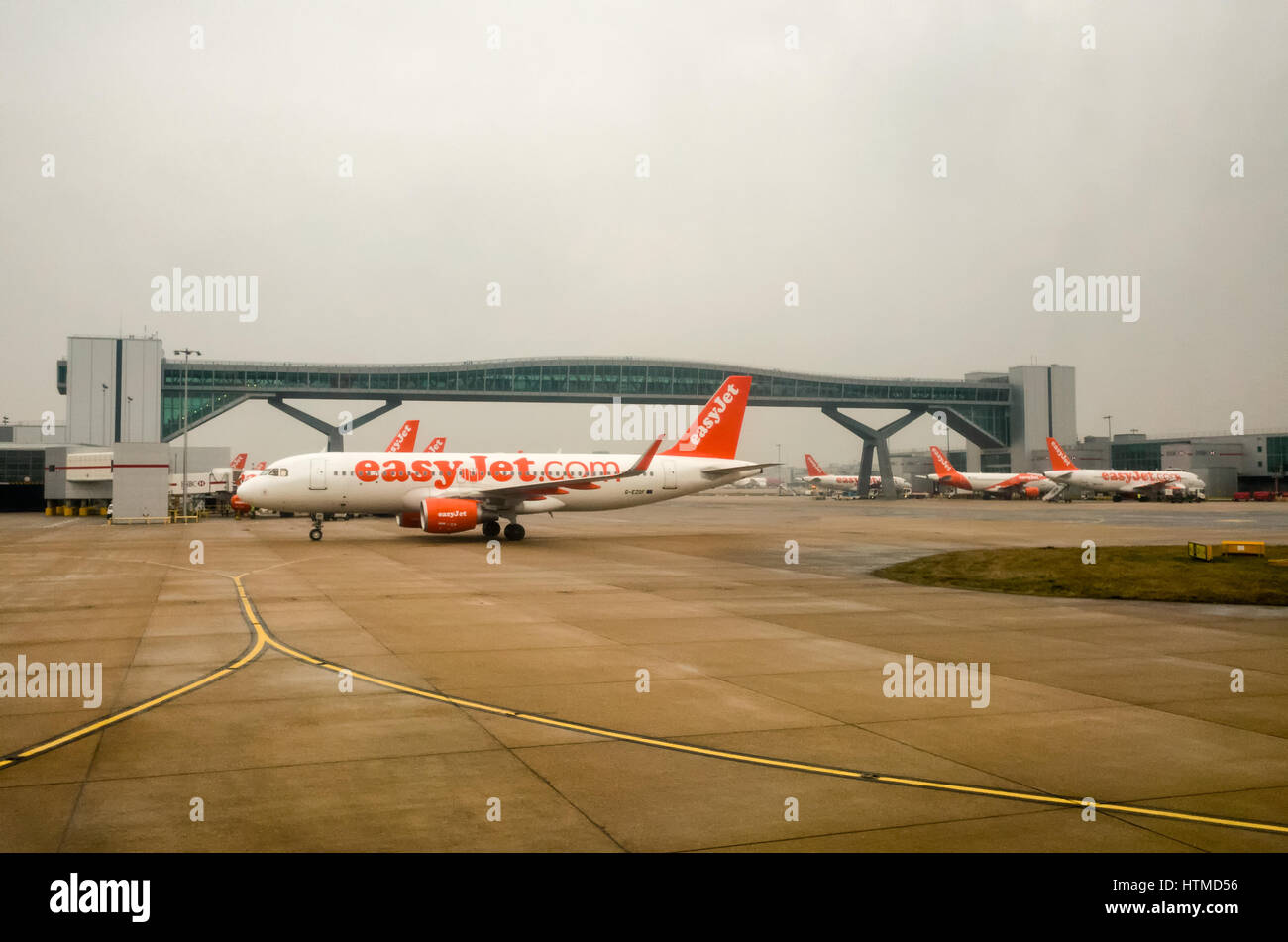 London Gatwick. England UK.  EasyJet aeroplanes on London Gatwick airport runway with a foot bridge that crosses - Stock Image